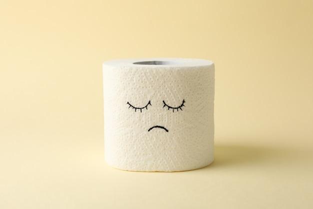 Туалетная бумага с грустным лицом на бежевом
