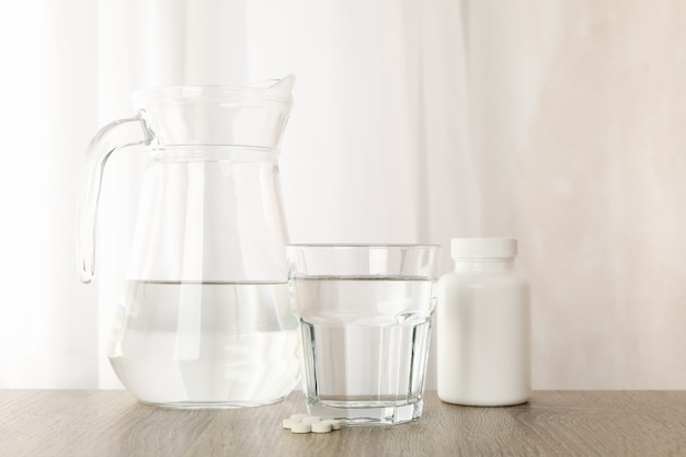 水差しと水のガラス、および木製のテーブルの丸薬をクローズアップ