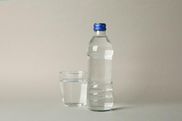 Бутылка и стакан с водой на сером, место для текста