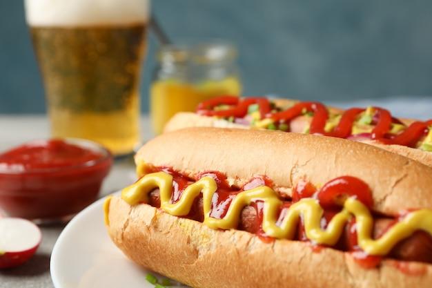 Вкусные хот-доги, пиво и картофель фри на сером столе