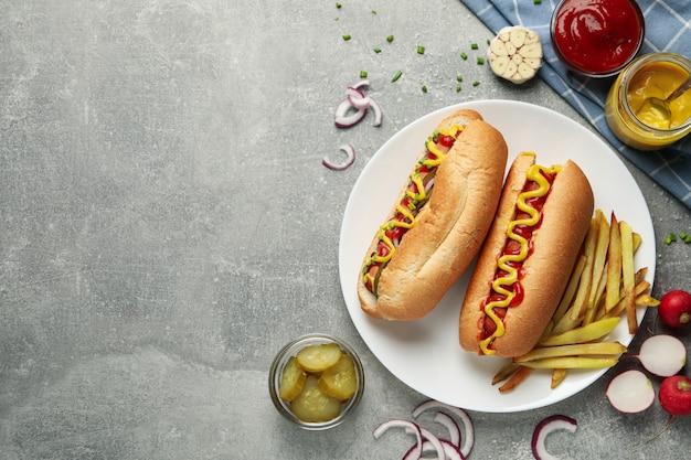 灰色のテーブル、トップビューでおいしいホットドッグとフライドポテト