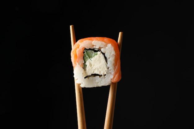 Палочки для еды с суши ролл на черной поверхности. японская еда