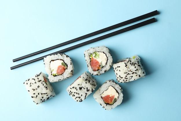 Палочки для еды и суши роллы на синей поверхности. японская еда
