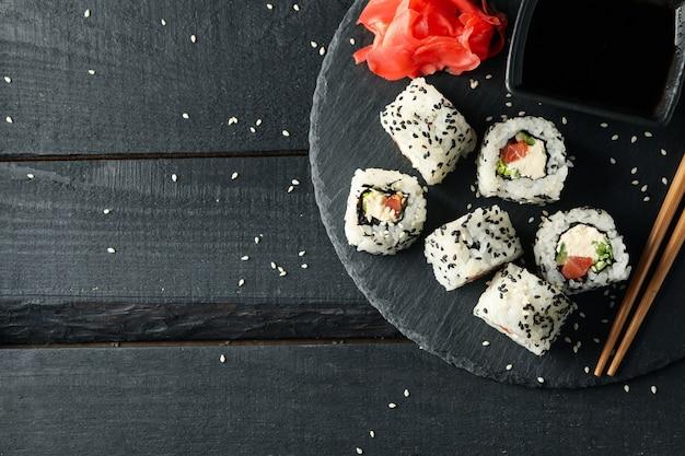 Поднос с вкусные суши роллы на деревянной поверхности. японская еда