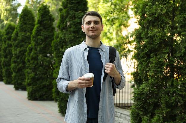 若い学生はバックパックと一杯のコーヒーを保持します。