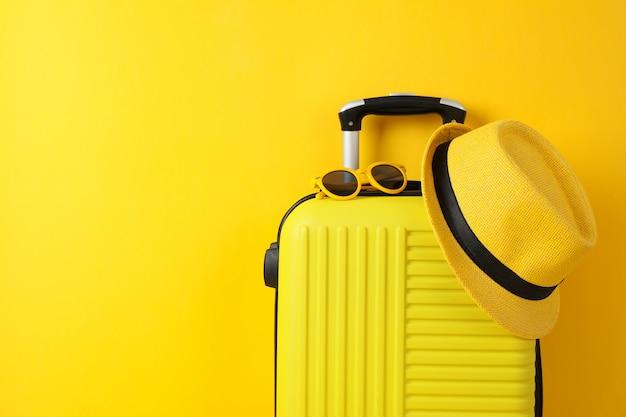 サングラスと帽子に黄色のトラベルバッグ