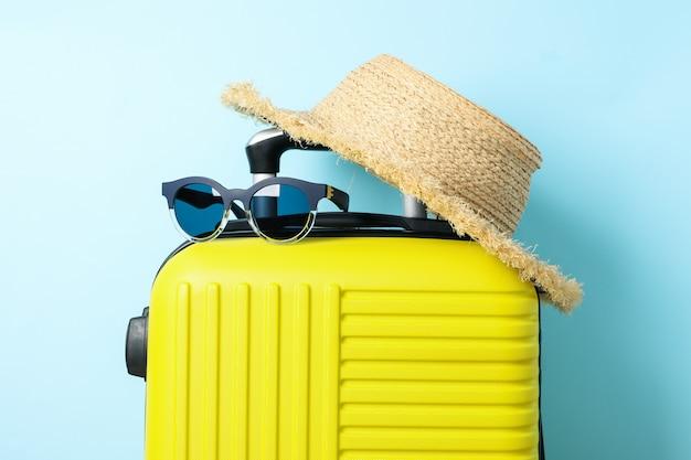 サングラスと青の帽子と旅行バッグ