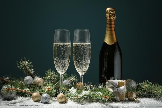 Бокалы для шампанского и бутылка на украшенном пространстве, место для текста