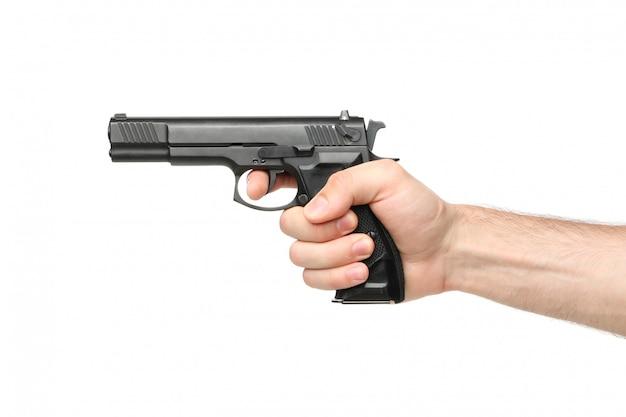 Мужская рука держит черный пистолет, изолированный на белом