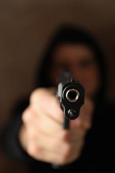 Мужчина держит пистолет. выборочный фокус. разбойник. насилие