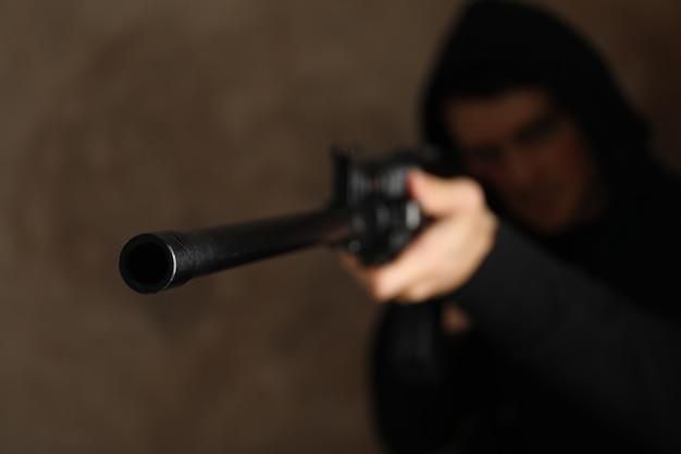 Мужчина в капюшоне держит пистолет. выборочный фокус. разбой