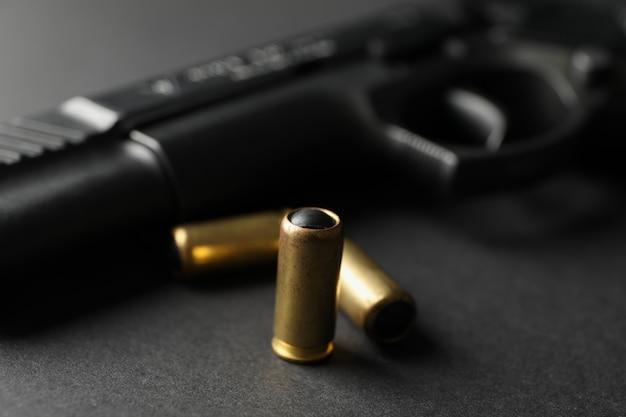 Пистолет и травматические пули на черном. оружие самообороны