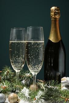 Бокалы для шампанского и бутылка на украшенном пространстве, крупный план