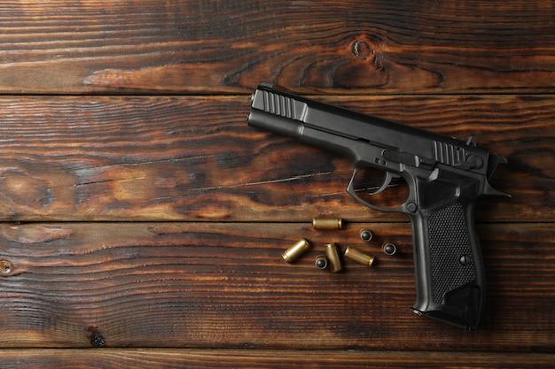 Пистолет и пули на деревянном. оружие самообороны