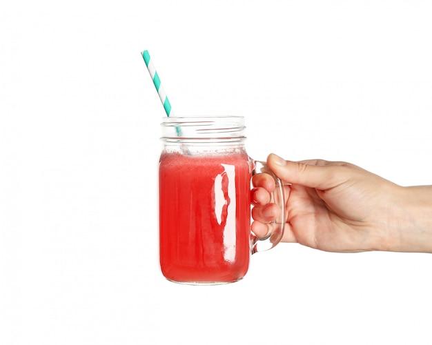 女性の手を保持するホワイトスペースで分離されたスイカジュースのガラス瓶