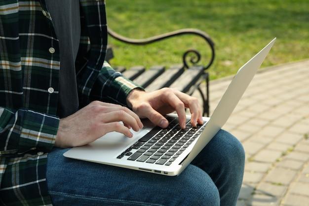 ノートパソコンを持つ男は公園で動作します。アウトドアワーク