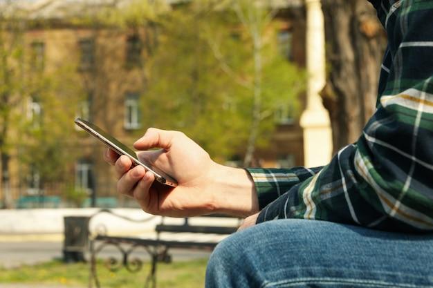 シャツを着た男性が公園に座っているスマートフォンを使用しています