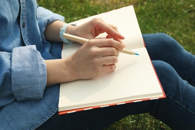 女の子は、緑の芝生の上に座って屋外を描画します。創造性の概念
