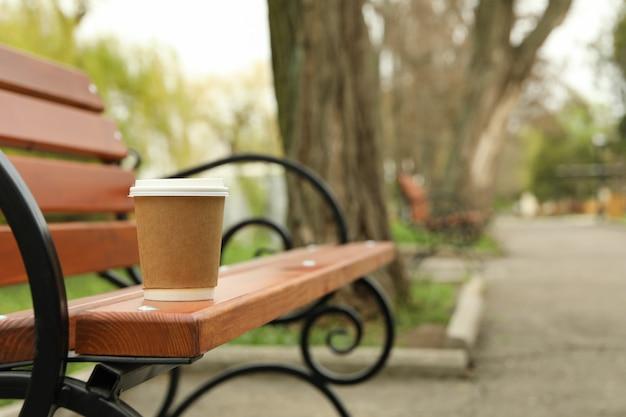 公園のベンチ、テキスト用のスペースに空白の紙コップ