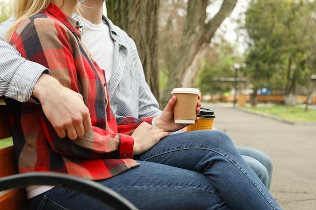 公園で座っているカップルとコーヒーを飲む