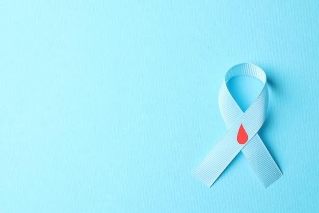 Сахарный диабет. синяя лента осведомленности с украшенной каплей крови на синем фоне