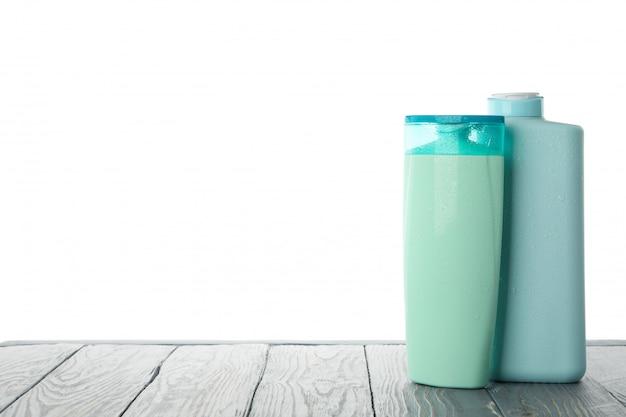 白い背景に分離された木製のテーブルの空白の化粧品ボトル
