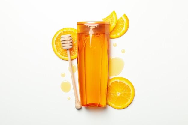シャンプーボトル、オレンジスライス、白い背景の上のひしゃく。自然派化粧品
