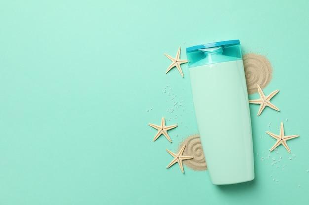 シャンプー、ヒトデ、ミントの背景に砂のボトル