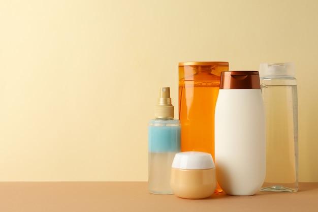 ベージュ色の背景、テキスト用のスペースに空の化粧品ボトル