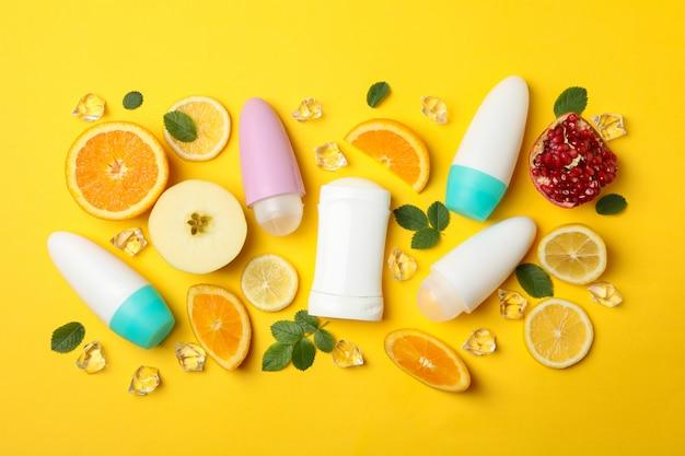 体の消臭剤、氷、黄色の背景にフルーツ、テキスト用の空白