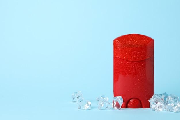 Дезодорант для тела и лед на синем фоне, пустое пространство для текста