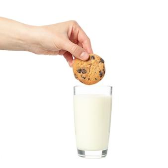 女性は、白い背景で隔離のミルクのガラスのクッキーを浸す