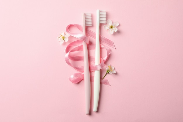 歯ブラシ、リボン、ピンクの背景、テキスト用のスペースの花