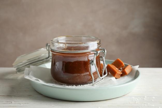 塩キャラメルとキャンディー木製スペース、テキスト用のスペースのガラスの瓶