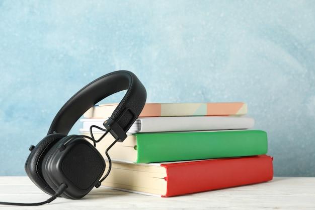 書籍と青いスペース、テキスト用のスペースに対するヘッドフォン