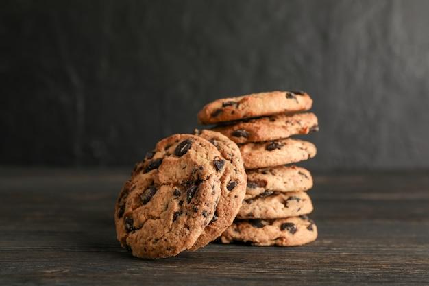 Стог вкусных печений обломока шоколада на деревянном столе.