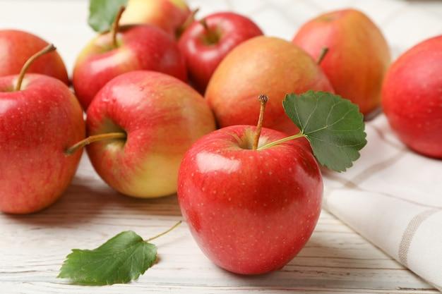 Яблоки и полотенце на белом деревянном столе