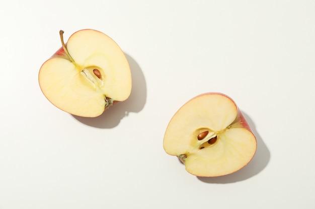 Половинки яблока на белом столе