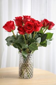 Ваза с букетом красных роз на деревянный стол