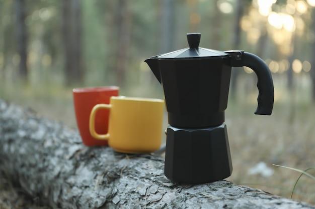 松の幹にコーヒーメーカーとカップ。美しい森、テキスト用のスペース