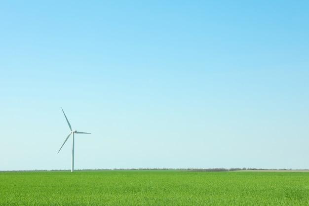 Ветротурбина в поле зеленой травы, космос для текста. красивая весенняя зелень