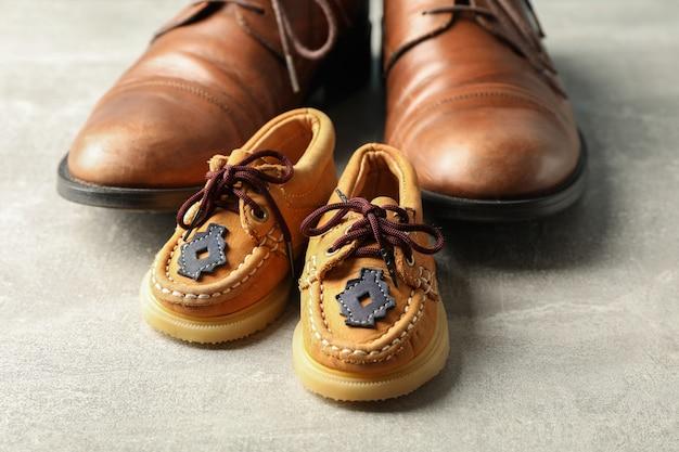 Коричневые кожаные туфли и детская обувь на сером фоне