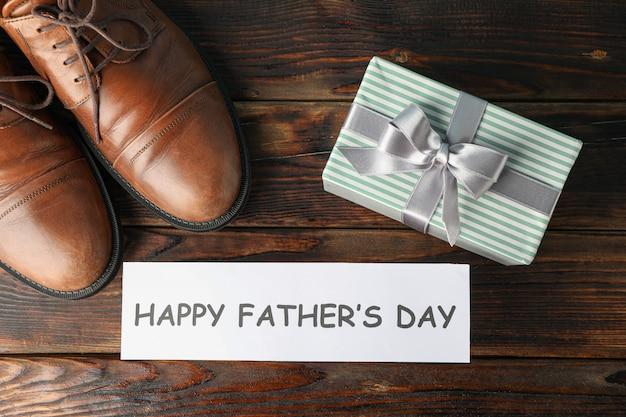 Коричневые кожаные ботинки, надпись счастливый день отцов и подарочная коробка на деревянном фоне