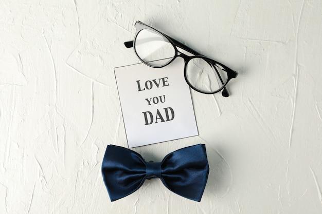 Надпись люблю тебя, папа, синий галстук-бабочка и очки на белом фоне, место для текста и вид сверху