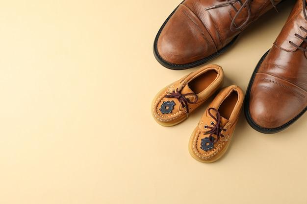 Коричневые кожаные туфли и детская обувь на цветном фоне, место для текста и вид сверху