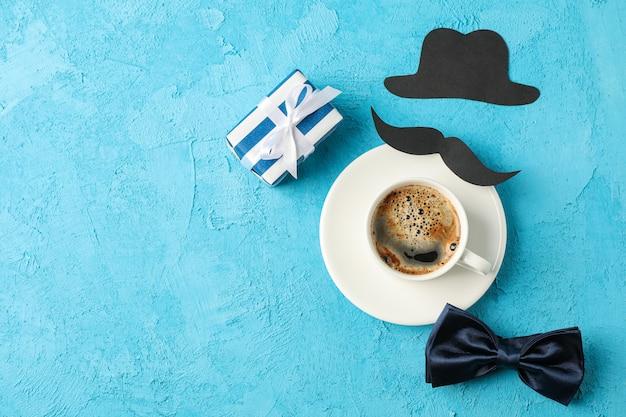 Чашка кофе, галстук-бабочка, подарочная коробка, декоративные усы и шляпа на синем фоне, место для текста и вид сверху