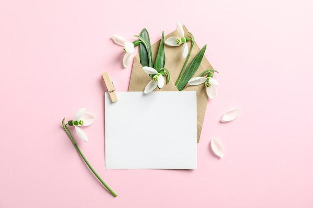 Конверт с цветами подснежника и бумага на цветном фоне