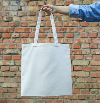Женская рука держит сумку против кирпичной стены