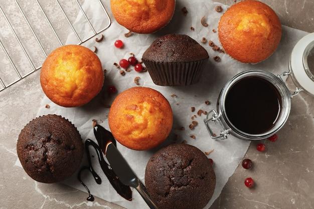 Композиция с вкусными кексами, ягодами, шоколадом и бумагой для выпечки