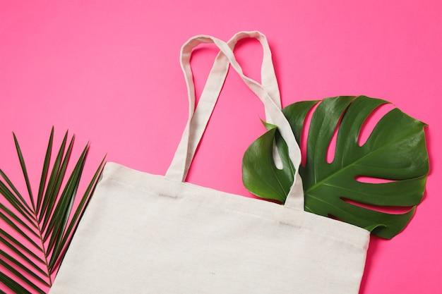 Эко-сумка и пальмовые листья на цветном фоне